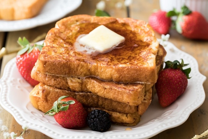 French toast topped with melted butter on white plate