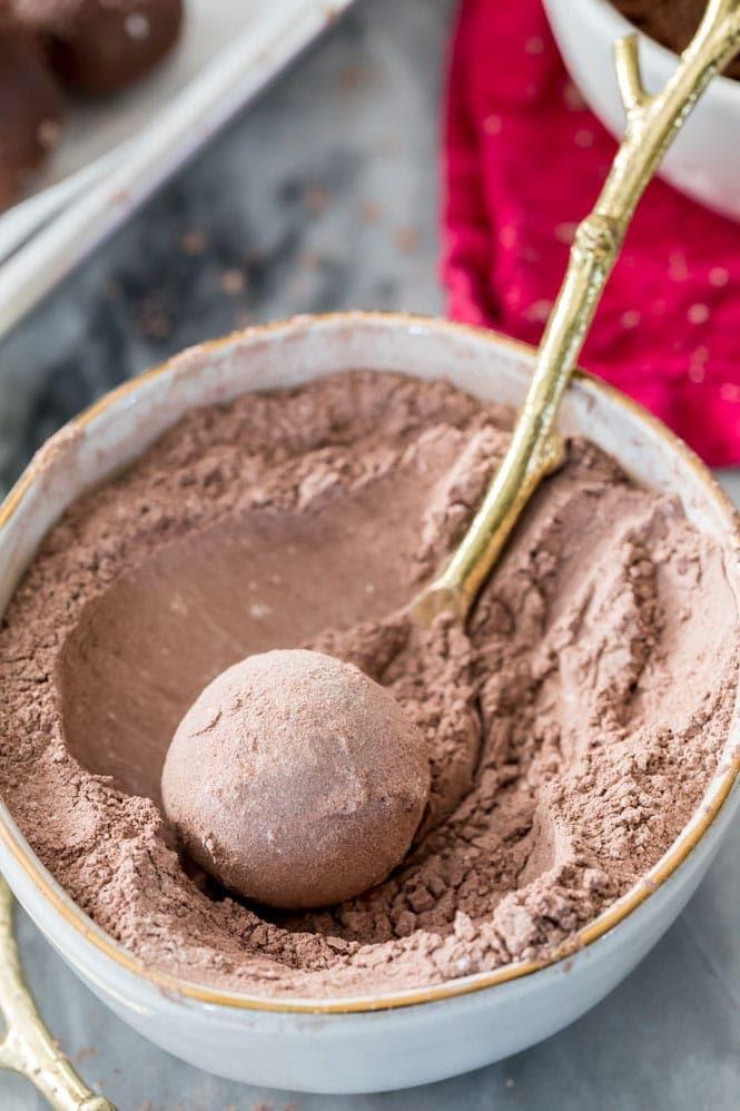 Rolling chocolate truffle in a cocoa sugar powder