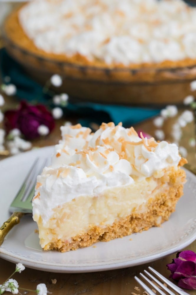 Slice of coconut cream pie on white plate
