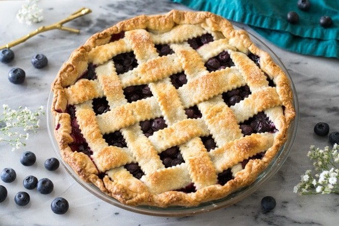 Freshly baked blueberry pie on marble slab