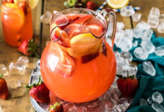 Pitcher of strawberry lemonade sitting on ice