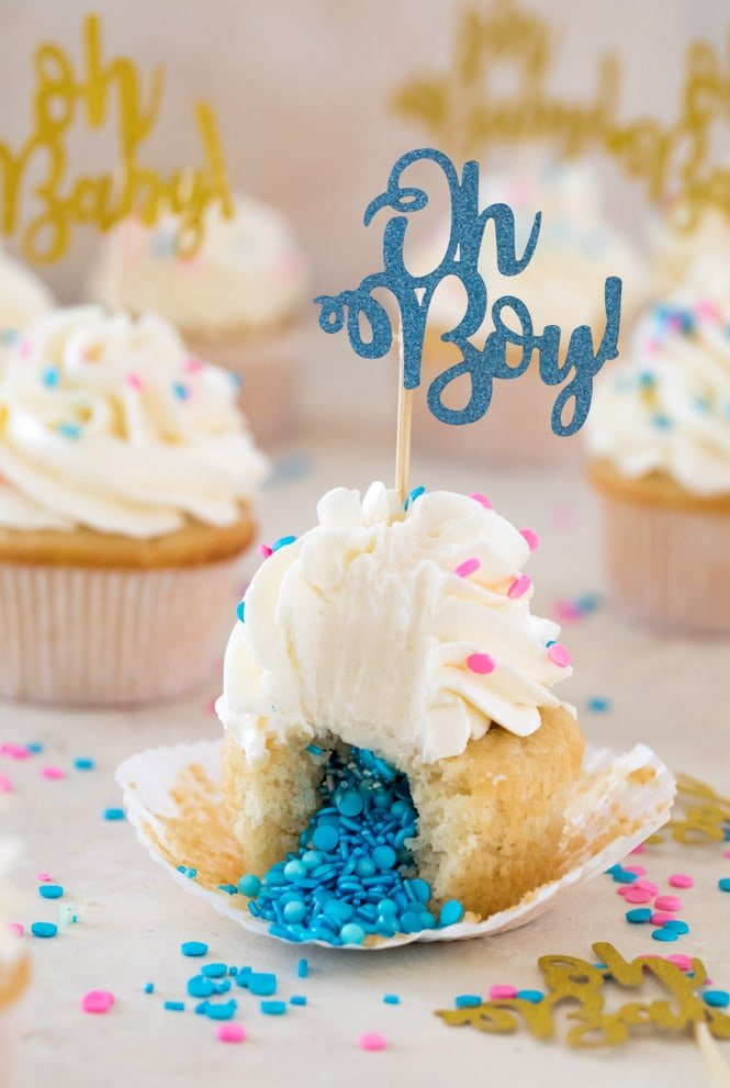 Gender reveal cupcake cut in half with blue sprinkles pouring out of center