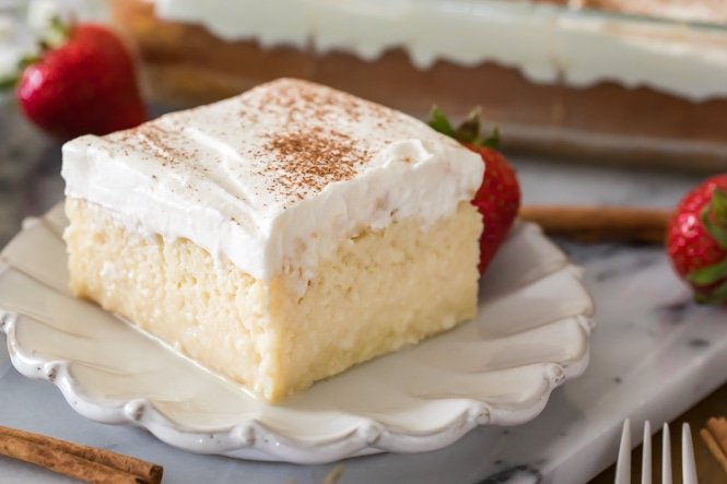 Slice of tres leches cake on white plate