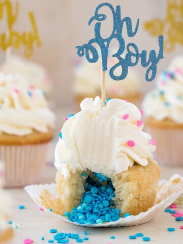 "Cupcake broken open to reveal insides topped with frosting and ""oh Boy!"" decoration"