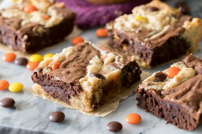 Freshly cut squares of warm peanut butter brownies on marble board