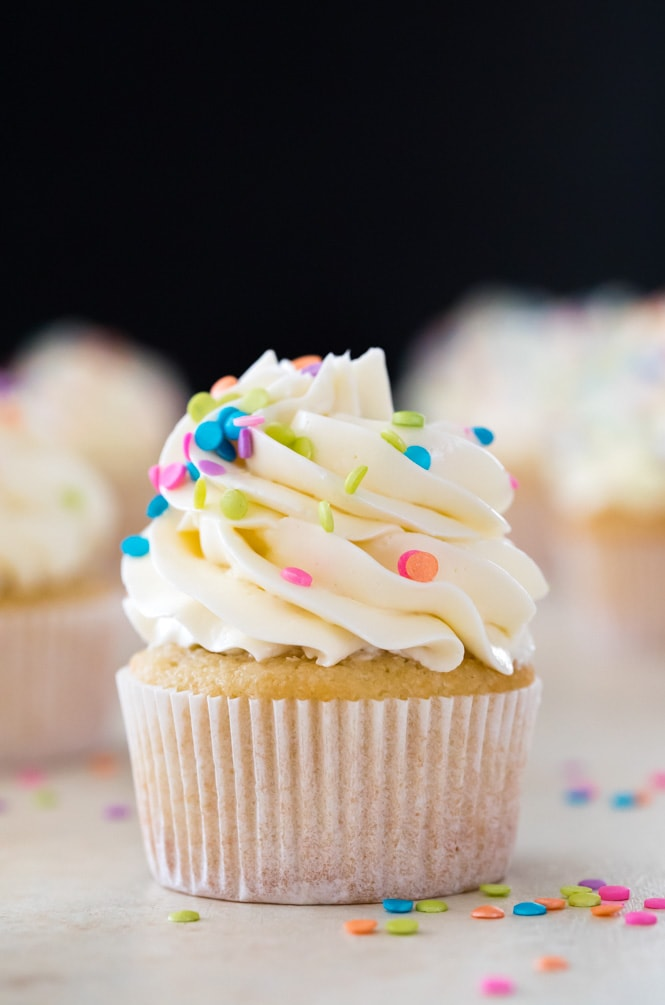 White icing piped on vanilla cupcake with black backdrop