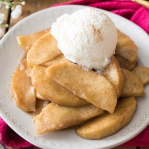 Fried apples topped with ice cream on white plate