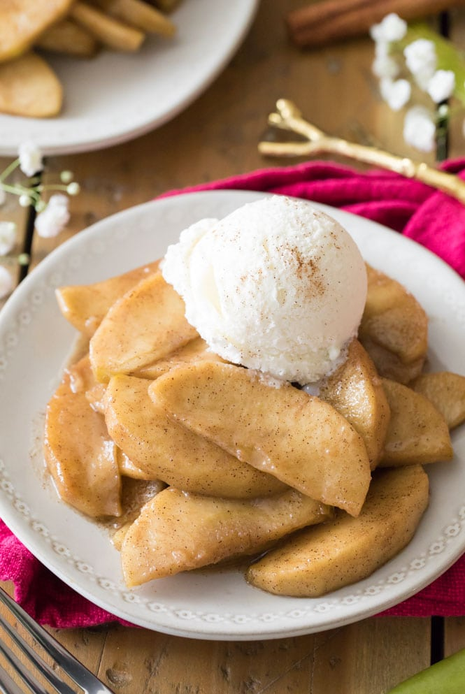 Fried apples on white plate with scoop of vanilla ice cream