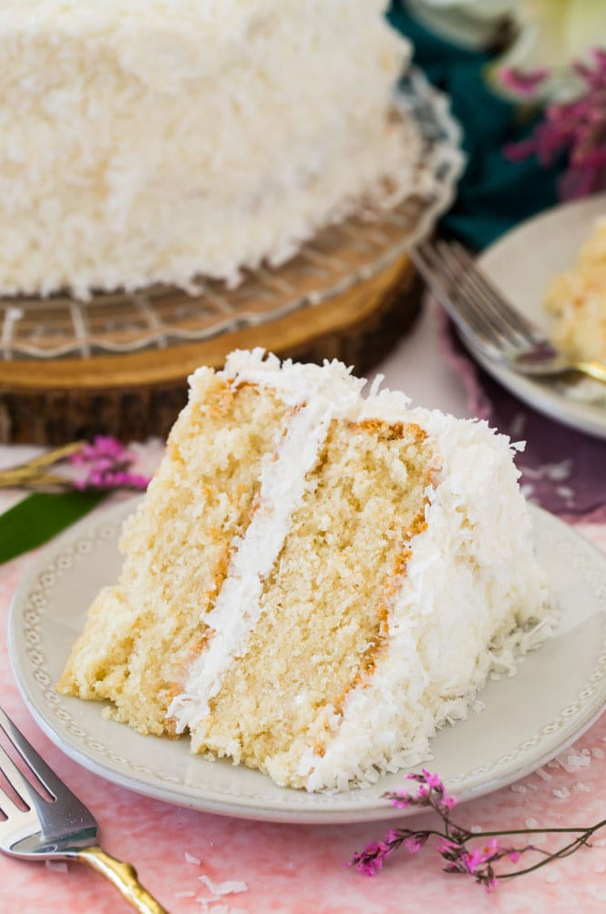 Slice of layered coconut cake on white plate on pink backdrop