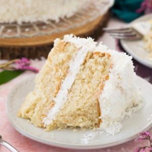 Slice of coconut cake on white plate with bite taken