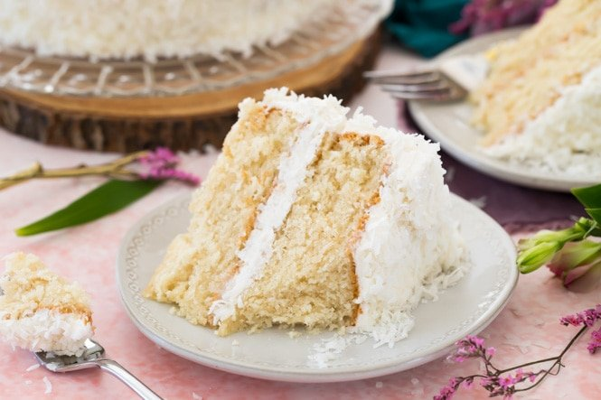 Slice of frosted coconut cake on a white plate with a forkful out of it to show soft interior
