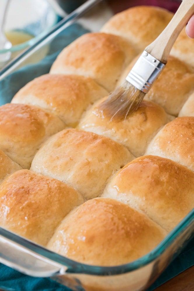 Brushing freshly baked dinner rolls with melted honey butter