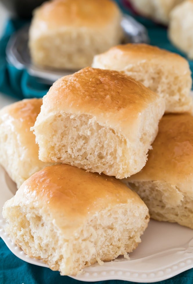 Soft fluffy dinner rolls on a white plate