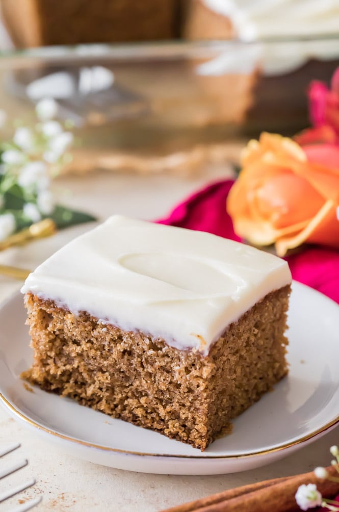 Slice of spice cake with cream cheese frosting on white plate