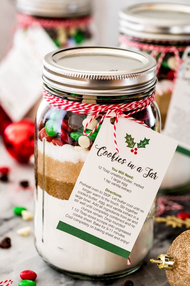 Clear mason jar of cookie mix with pretty layers and holiday colored toppings