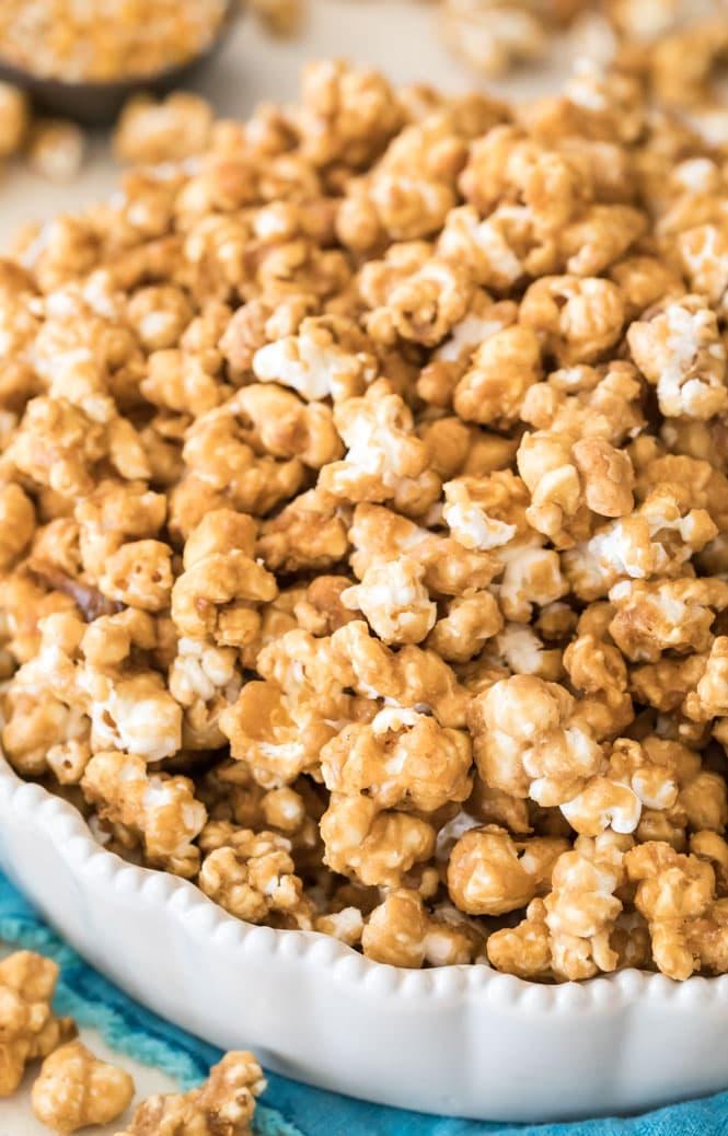 Caramel popcorn piled high in a white dish, showcasing the shiny coating.