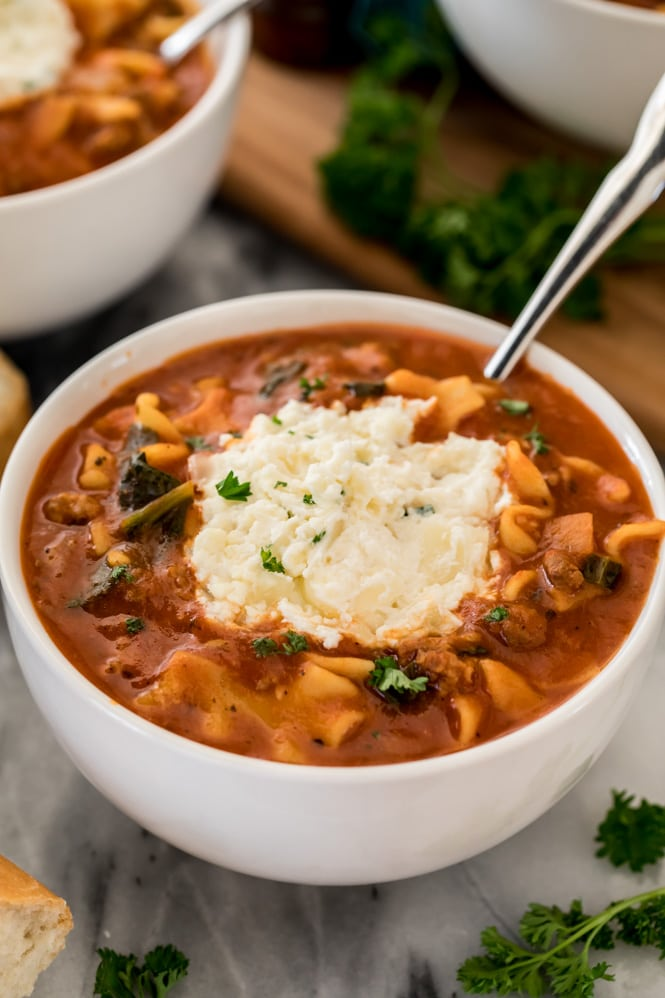 Lasagna soup recipe in a white bowl with ricotta topping