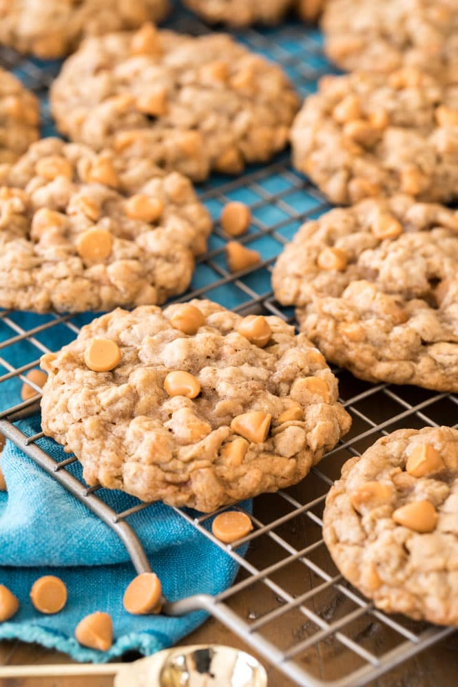 Oatmeal scotchies cooling on a gold wire wrack with a blue towel underneath