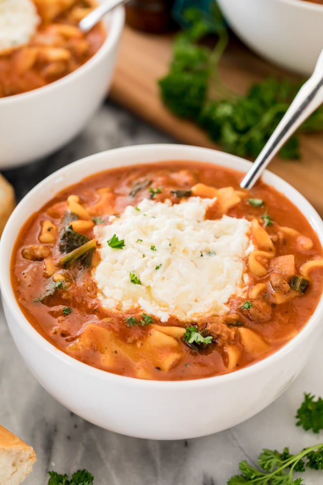 White bowl with lasagna soup topped with ricotta cheese