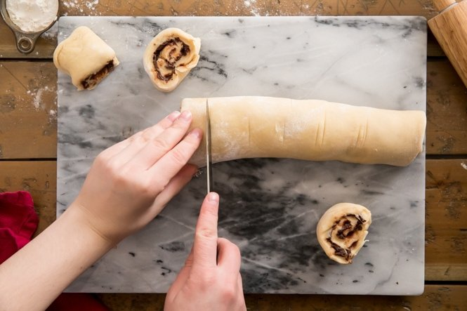 Cutting log of chocolate sweet roll dough on marble