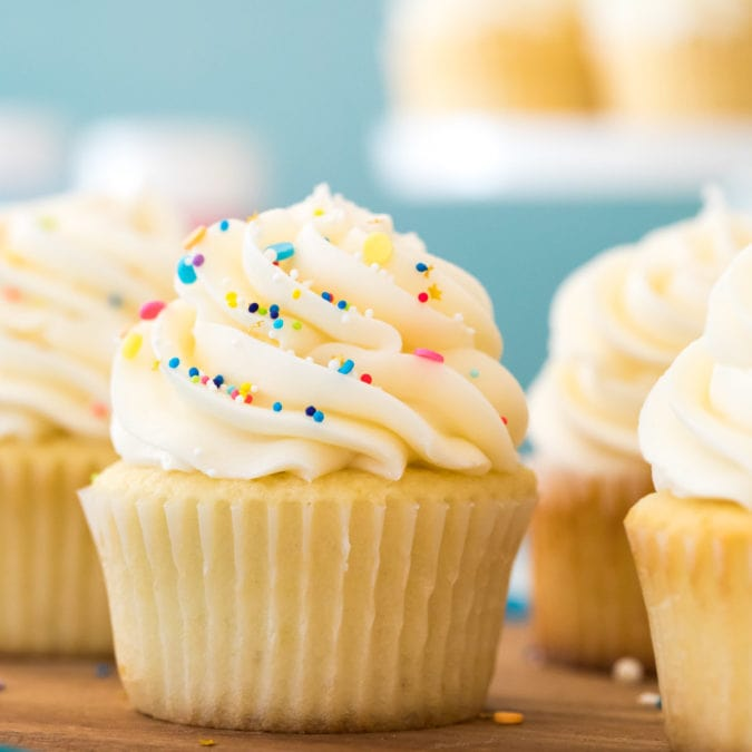 Buttercream frosting topped with sprinkles on vanilla cupcake