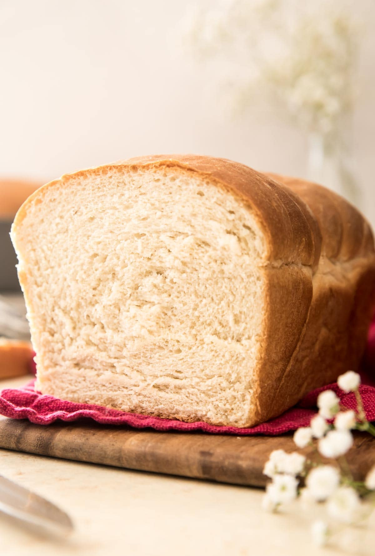 loaf of bread on a red towel on a wooden cutting board with white flowers in foreground and background