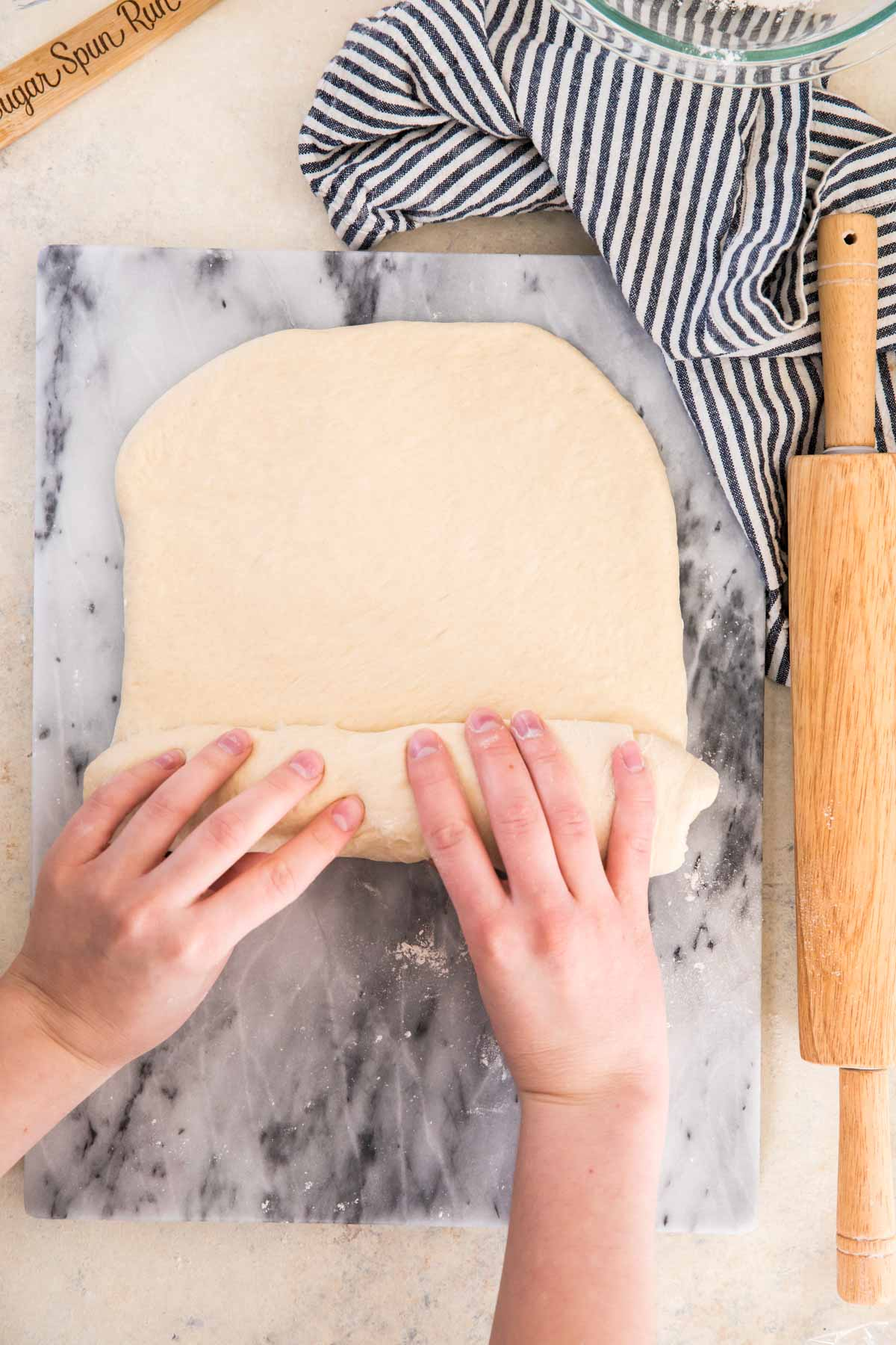 rolling dough into a loaf on a marble cutting board