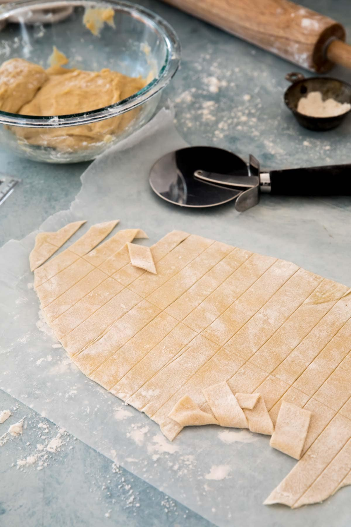 Dough rolled paper thin and cut into strips. pizza cutter, rolling pin, flour, and glass bowl with more dough in background