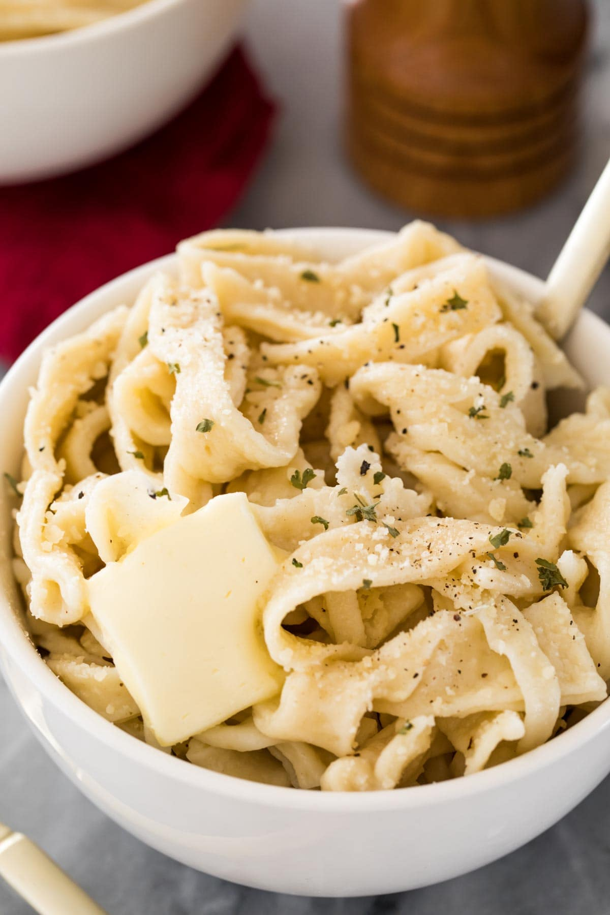 cooked egg noodles with butter in white bowl
