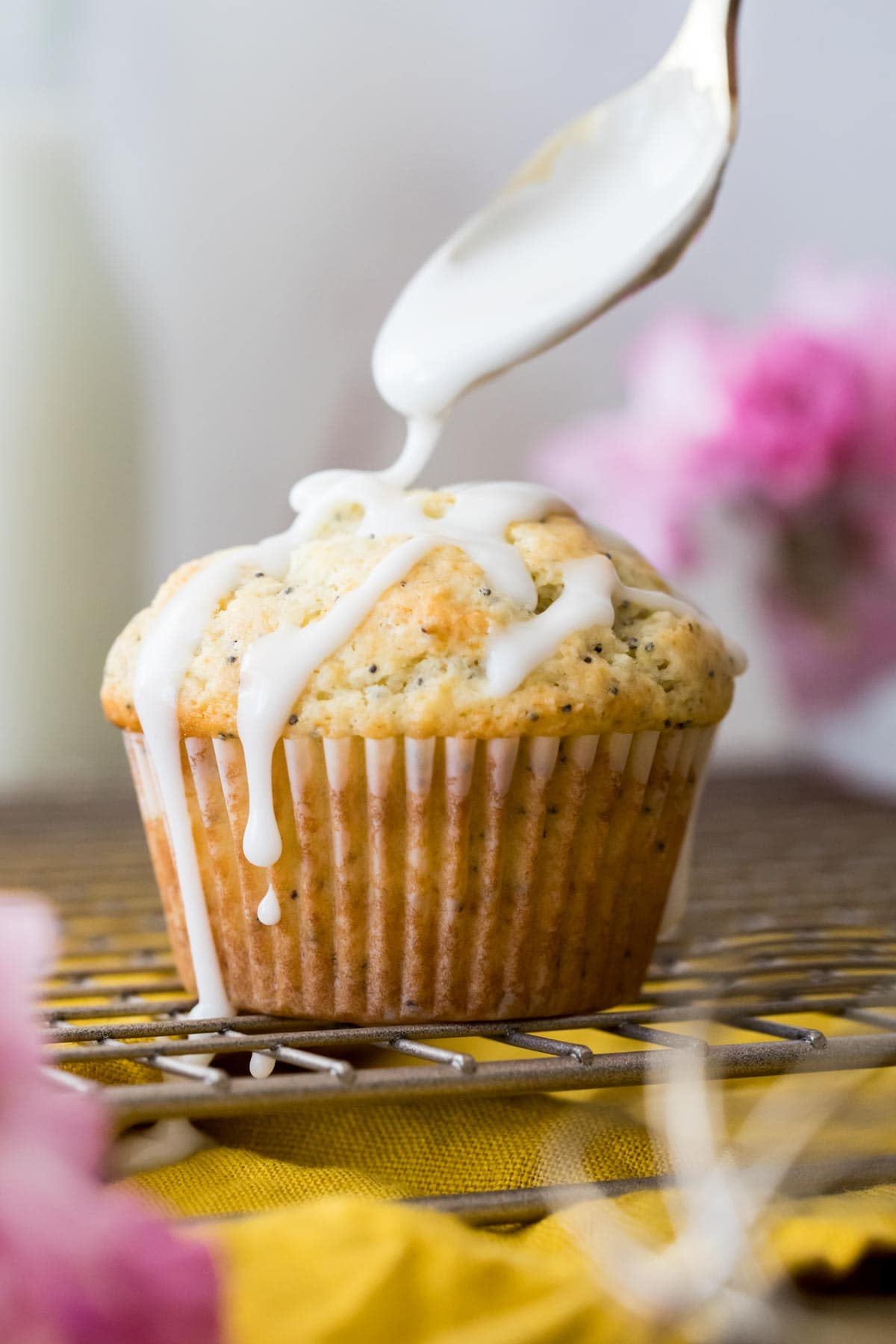 Drizzling icing on lemon poppy seed muffin