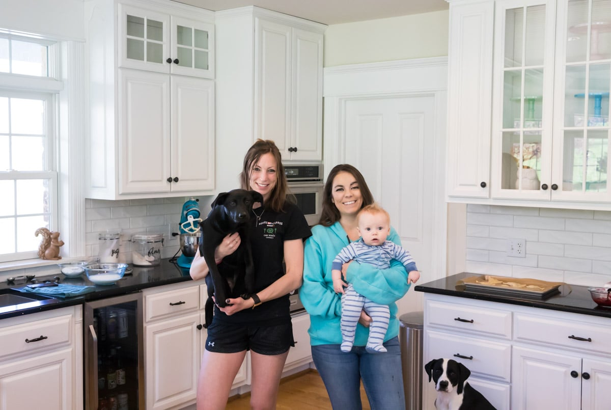 two girls, one holding a puppy and the other holding a baby