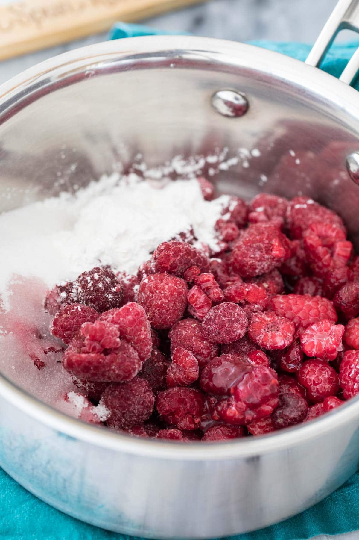 raspberries and sugar in silver-colored saucepan