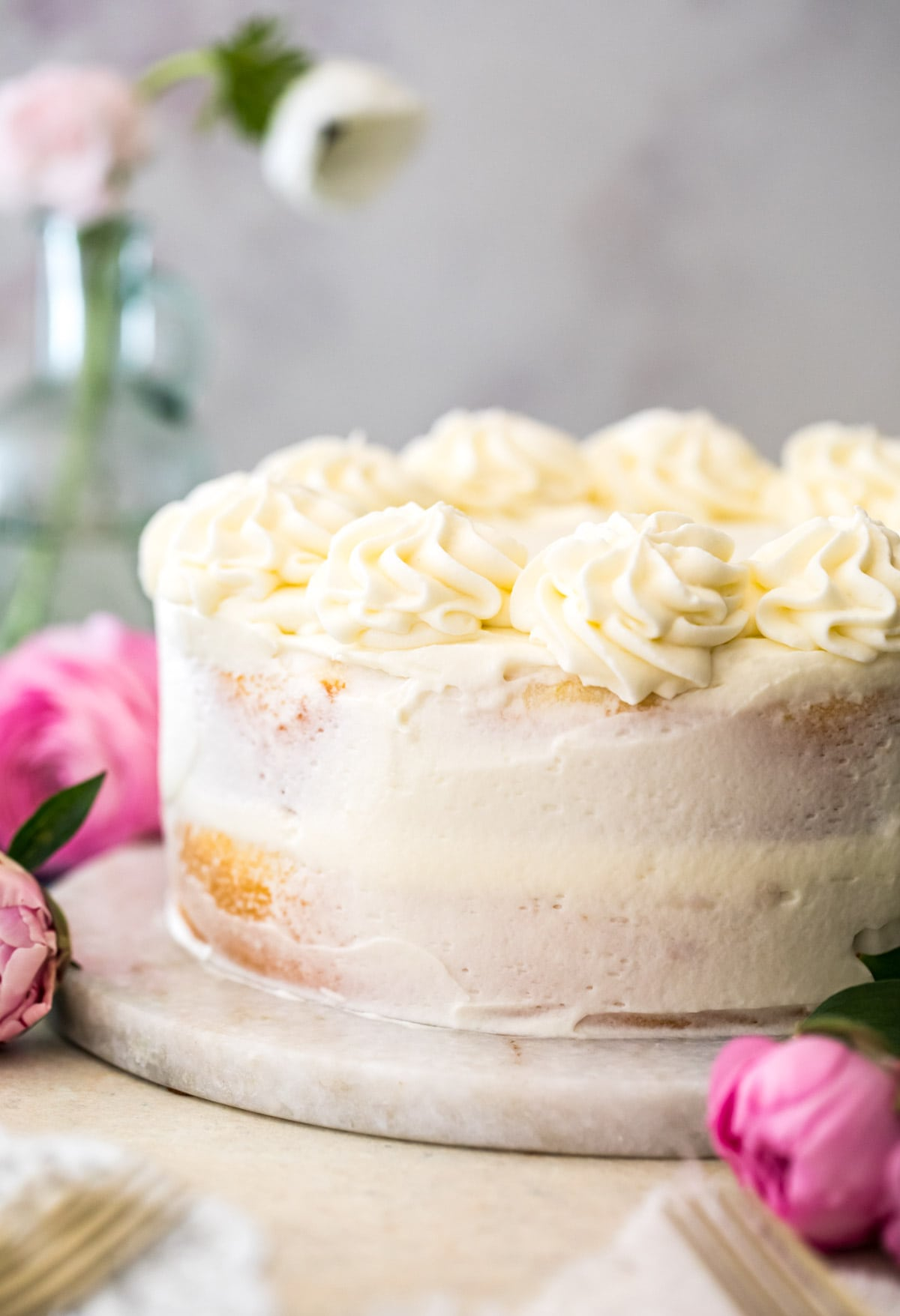 white frosted cake surrounded by pink flowers