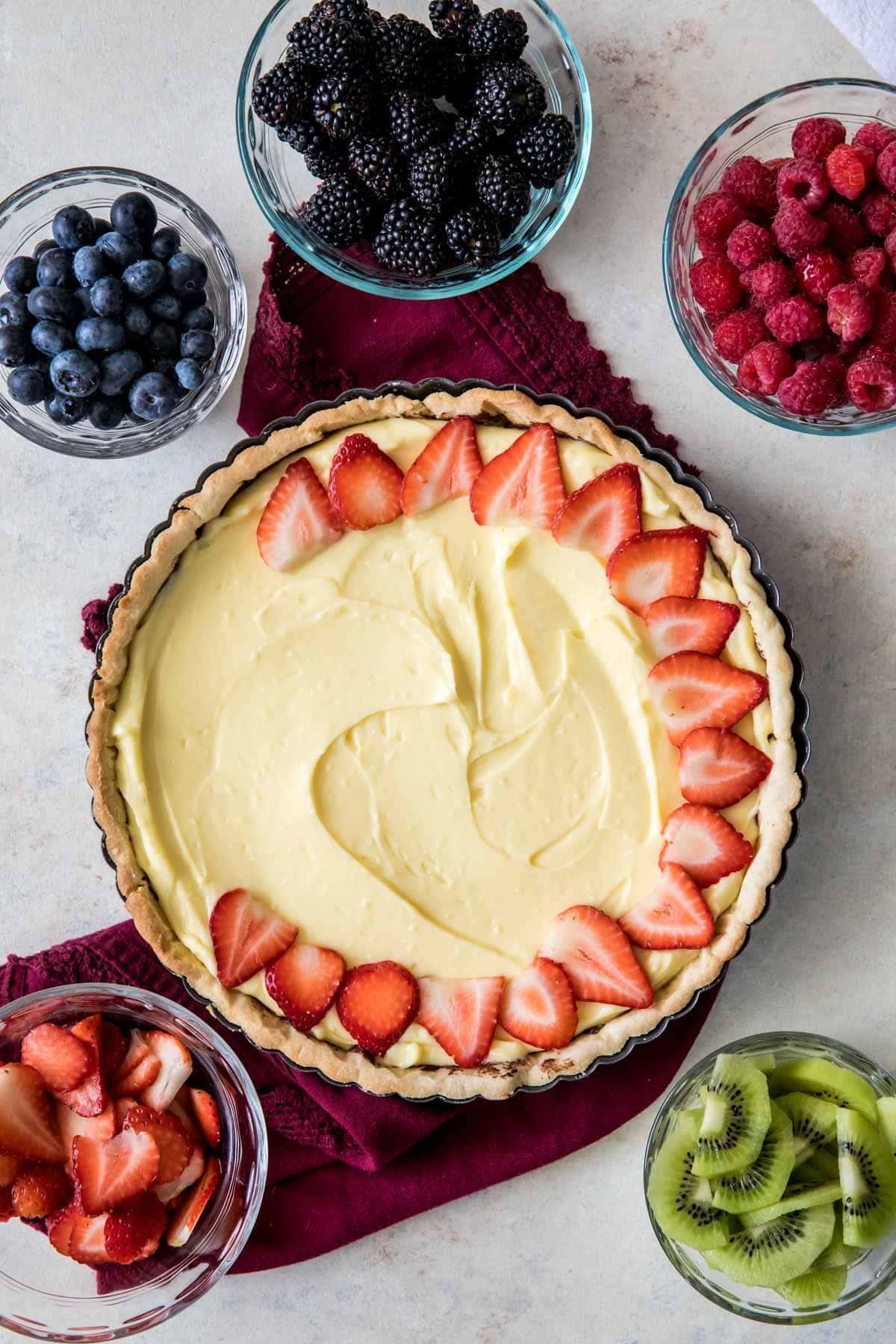 arranging strawberry slices over pastry cream