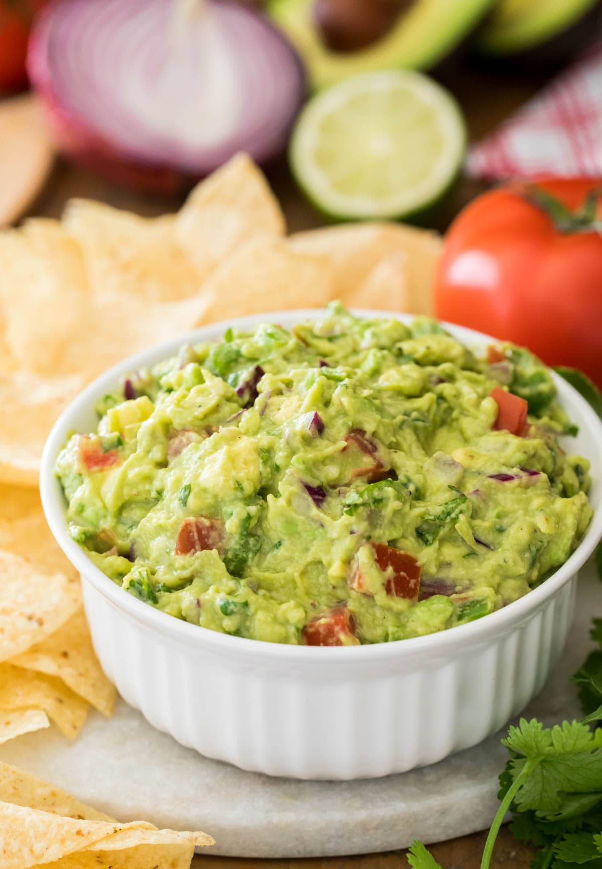 guacamole in white bowl surrounded by corn chips