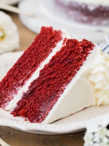 Slice of frosted Red Velvet cake on a white plate