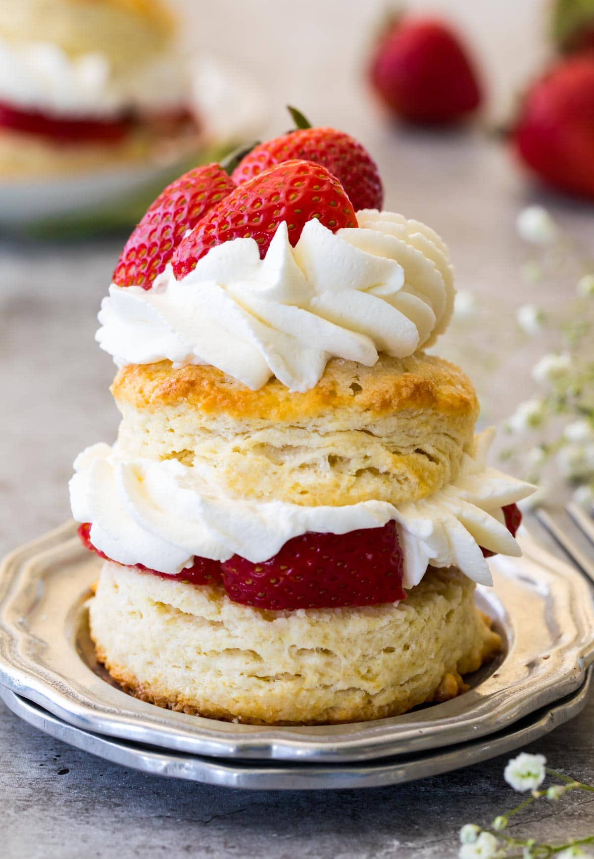 shortcake stacked with whipped cream and strawberries on silver plate