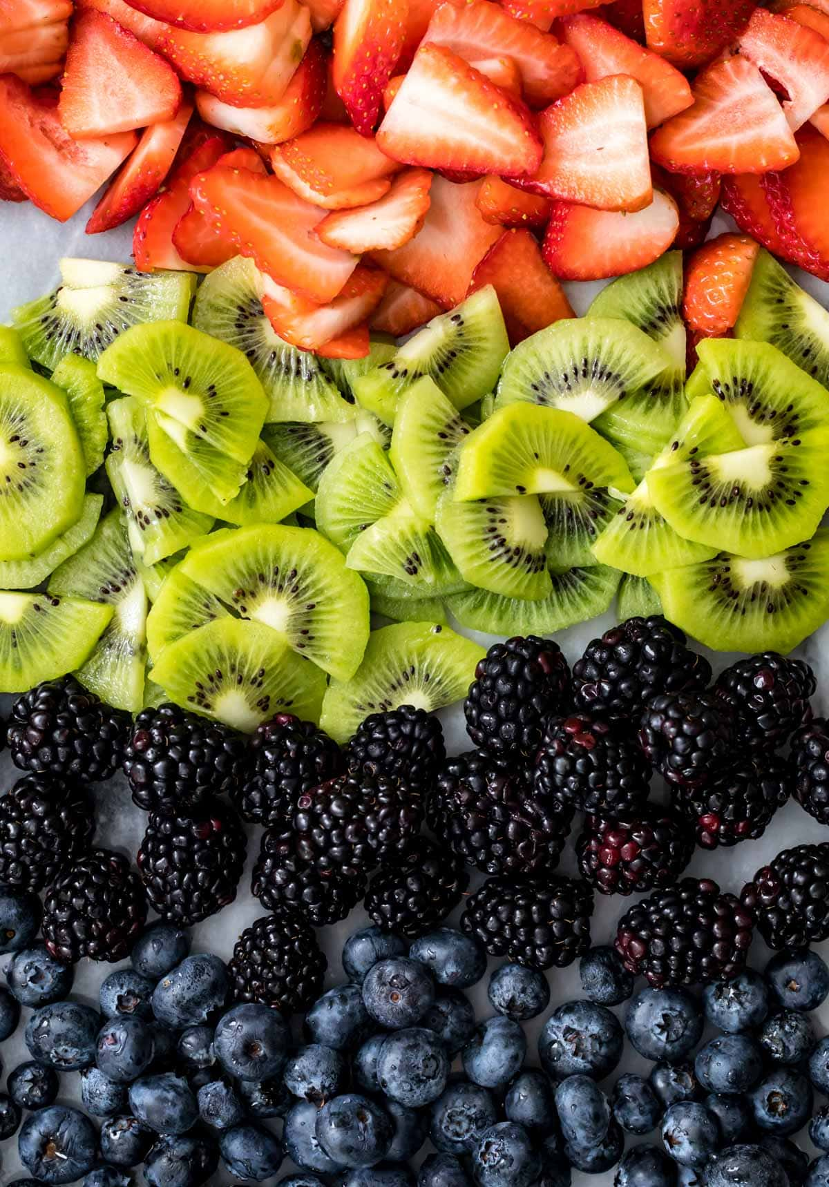 Array of fruit: strawberry and kiwi slices, blackberries and blueberries