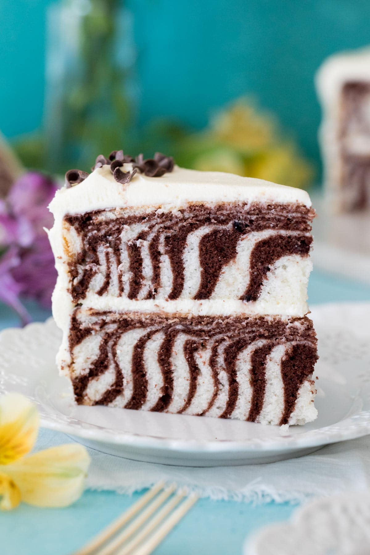 slice of striped zebra cake standing upright on white plate