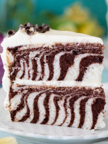 slice of striped zebra cake standing upright on white plate