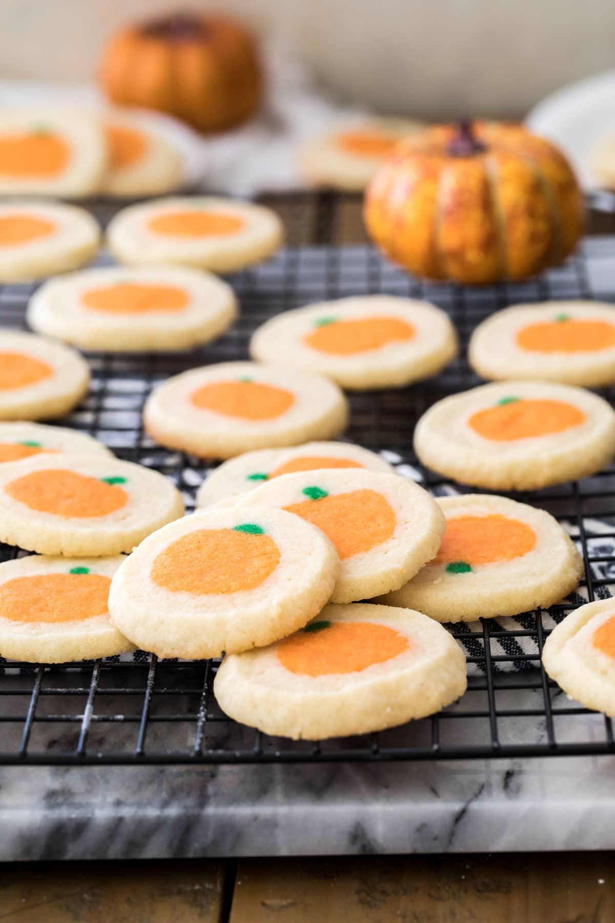 pumpkin sugar cookies on black cooling rack