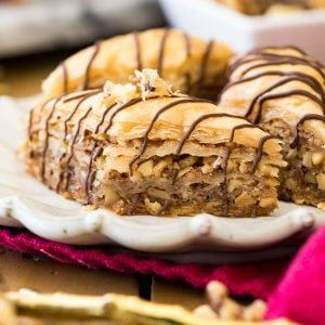 baklava with chocolate drizzle on white plate
