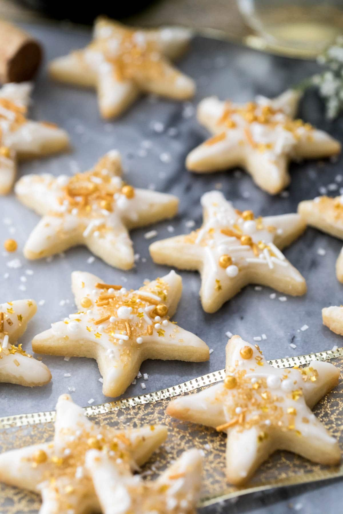 star cookies with champagne icing and sprinkles on marble
