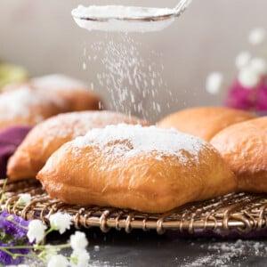 sprinkling powdered sugar over golden brown beignet