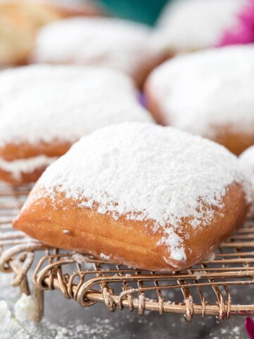 powder sugar-dusted beignet on cooling rack