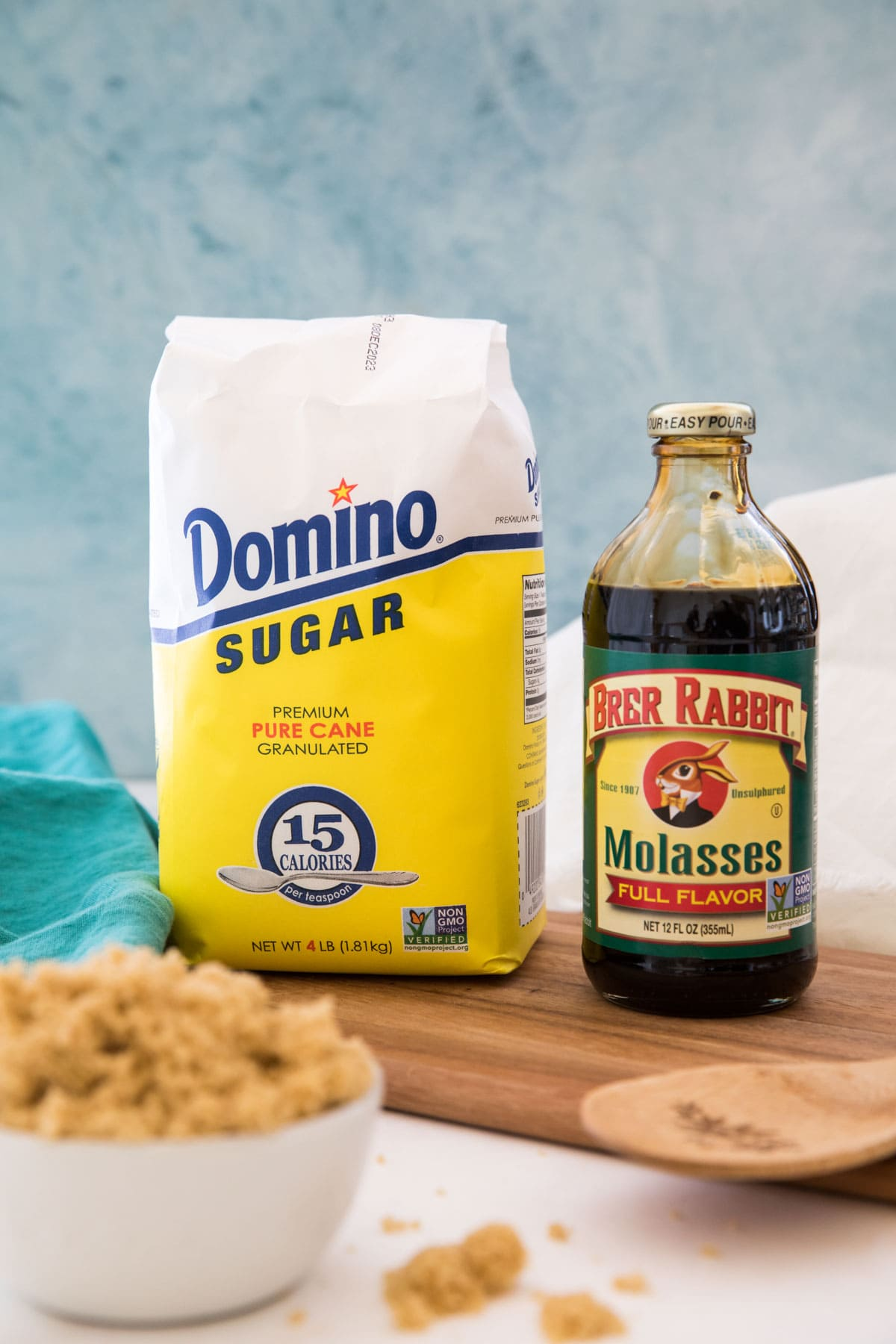 A bag of white sugar and a bottle of molasses