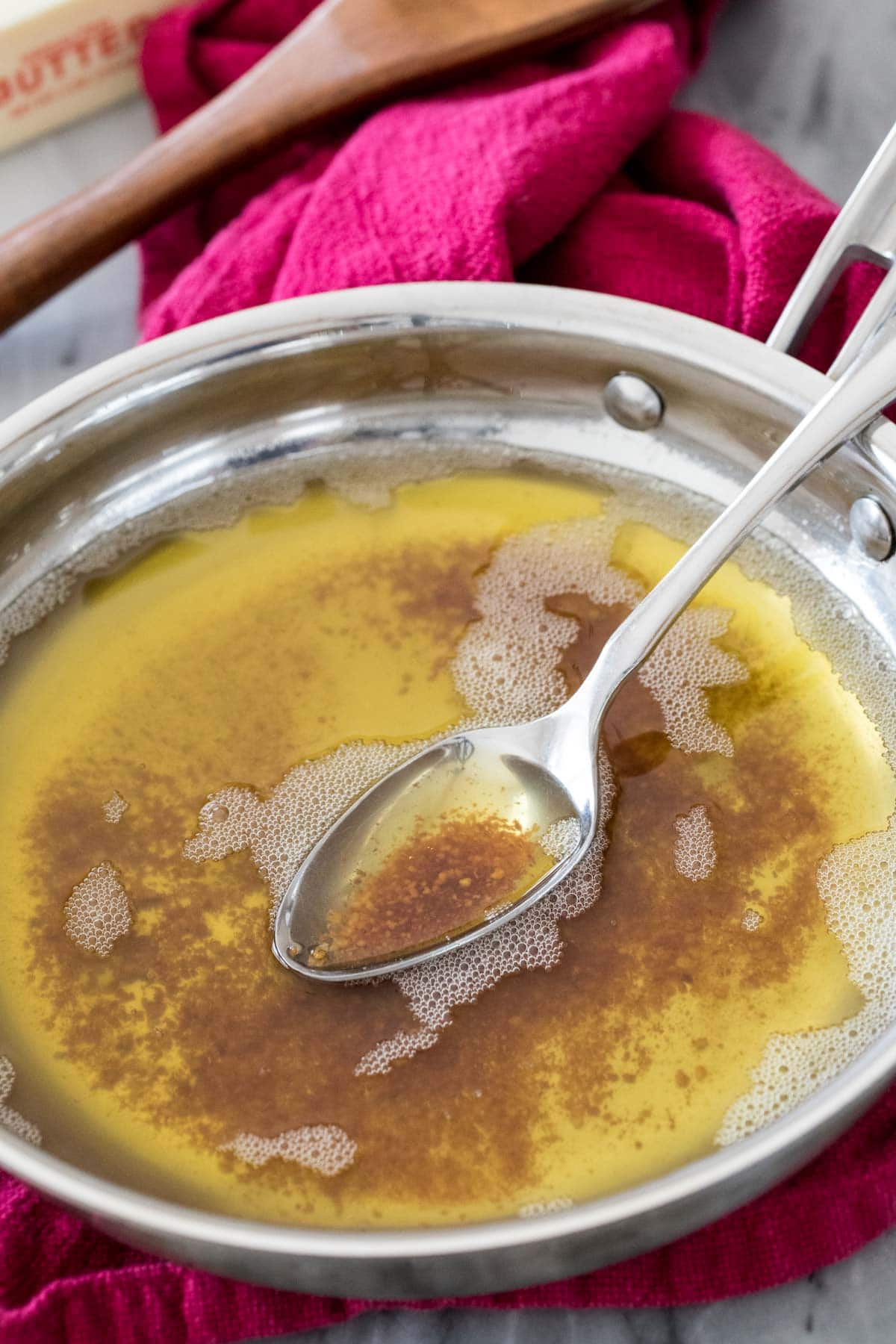 brown butter in saucepan with spoon showing browned bits