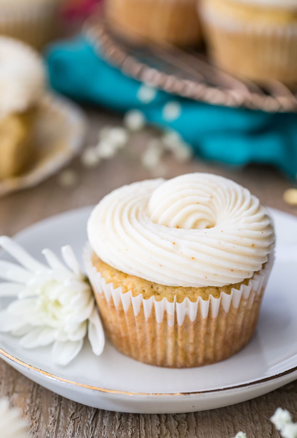 Banana cupcake on a white plate next to a white flower.