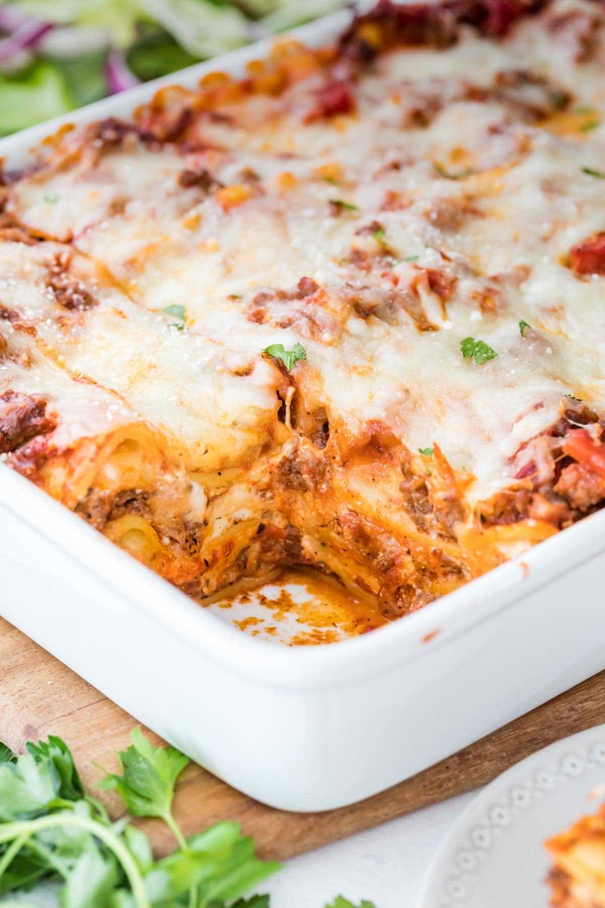Up close shot of lasagna with a piece cut out in white baking dish