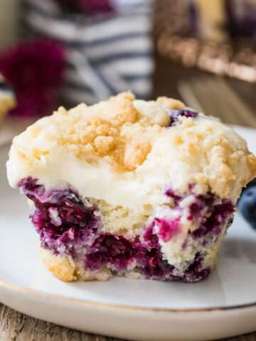 Closeup of blueberry cream cheese muffin with a bite taken out of it on a white plate.